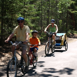 family riding bikes on community trail